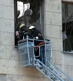 Firemen at work. Firemen saving a man hurt in a building crashing stock image
