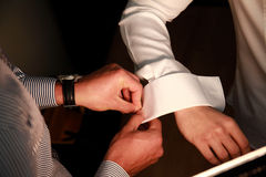 Firend helps groom wear cufflinks Royalty Free Stock Photo