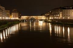 Firenze - Ponte Vecchio, gammal bro vid natt med reflexion in Arkivfoton
