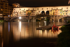 Firenze - Ponte Vecchio, Old Bridge by night, view from the rive. The Ponte Vecchio is a Medieval stone closed-spandrel segmental arch bridge over the Arno River Stock Images