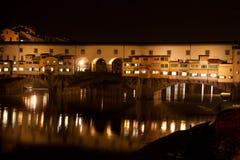 Firenze - Ponte Vecchio som är gammal överbryggar vid natt med reflexion Arkivbilder