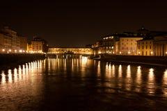 Firenze - Ponte Vecchio som är gammal överbryggar vid natt med reflexion i den Arno floden Arkivbild