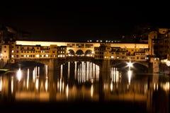 Firenze - Ponte Vecchio som är gammal överbryggar vid natt med reflexioner i den Arno floden Arkivbilder