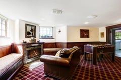 Οικογενειακό δωμάτιο πολυτέλειας με το firepalce και το πλούσιο κάθισμα αγάπης δέρματος Στοκ Εικόνες