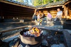 Firepit brûlant avec des amis préparant la nourriture dans le hangar Photos libres de droits
