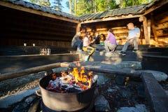 Firepit bruciante con gli amici che preparano pasto in tettoia Fotografia Stock