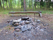 A firepit with a rustic wooden bench Stock Photo