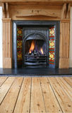 Fireplace 1. Close up of black coal fire with red floral surround and wooden mantel royalty free stock image