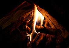 Fireplace. Open fireplace with flames and pieces of wood stock image