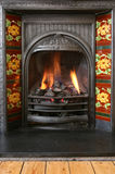 Fireplace 2. Close up of black coal fire with red floral tile surround Royalty Free Stock Photography