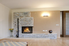 Fireplace. Firepace with stone fasade and beige wall Stock Photography
