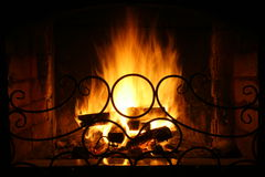 Fireplace. The fire is burning in the fireplace behind the fireguard Royalty Free Stock Image