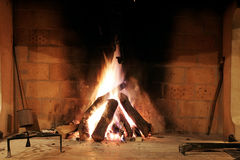 Fireplace. Logs are burning in a brick fireplace Stock Image
