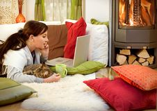 Fireplace 7. Woman is lying at a fireplace with cat and laptop Stock Photo