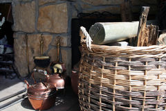 Fireplace. Basket of wood and copperware royalty free stock image
