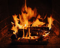 Fireplace with birch firewood and flame. Royalty Free Stock Photography