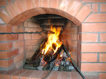Fireplace of brick in the house preparing sausage on a branch Royalty Free Stock Images