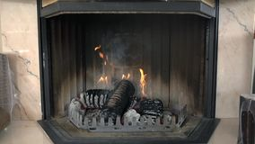 Fireplace with burning briquettes. We see a process of making the briquettes out of wood and using them to blaze up the fire in fireplace stock video footage
