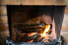 Fireplace and burning fire at home. Cosy bricks fireplace at home with flames of fire, burning logs and coal Royalty Free Stock Images