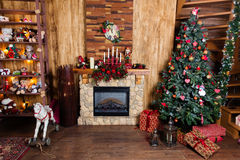 Fireplace and Christmas tree with gifts. Christmas decoration Stock Photos
