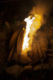 Fireplace. Close up of the bonfire with burning bamboo mat soft focus dark background Royalty Free Stock Images