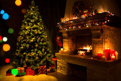 Fireplace and decorated Christmas tree and candles. Living room with fireplace and Christmas tree