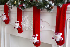 The fireplace decorated with red Xmas wool socks. With Santas and spruce branches royalty free stock photos