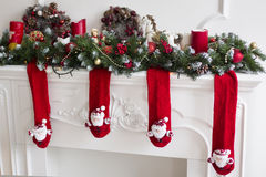 The fireplace decorated with red Xmas wool socks. The white fireplace decorated with red Xmas wool socks with Santas, candles, spruce branches, toys stock photo