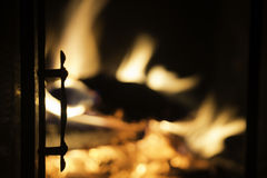 Fireplace door in silhouette with blazing fire in background. Cozy background stock photography