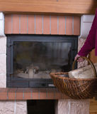 Fireplace and fire wood in a wattled basket Royalty Free Stock Photo