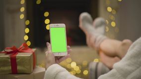 Fireplace flame and woman`s feet in motion. Girl looking at Christmas card on phone sitting static. Green screen seamless loop 4K motion photo cinemagraph stock video