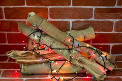 Fireplace with Garland. In the fireplace, firewood is decorated with a bright garland before Christmas Stock Photos