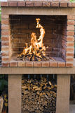 Fireplace grill. Outdoor fireplace grill with wood bucket royalty free stock images