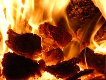 Fireplace - Hot Flames of Burning Coal Lumps and Heat. Radiant heating is warming interior of a house Stock Photography