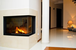 Fireplace. Interior of a private home - modern design fireplace with corner glass cover and a view of the downstairs hall stock image