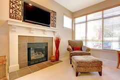 Fireplace with large TV above, elegant chair Royalty Free Stock Images
