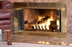 Fireplace with leather chair Stock Photos