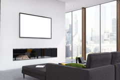 Fireplace living room, corner. Corner of a living room with a black sofa, a fireplace, a framed horizontal poster hanging above it and panoramic windows. 3d Stock Photo