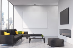 Fireplace living room, front view. Front view of a living room with a black sofa, a fireplace and a large plasma tv set hanging above it, a horizontal poster and Stock Image