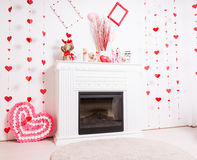 Fireplace Mantle Decorated for Valentines Day. Modern Fireplace Mantle in White Room Decorated for Valentines Day with Hearts royalty free stock photos
