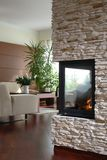 Fireplace in modern living room. With lit fire and glimpse of a corner of the living room Royalty Free Stock Image