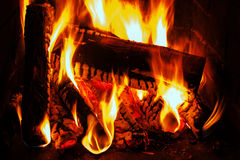 Fireplace with oak firewood and flame Royalty Free Stock Images