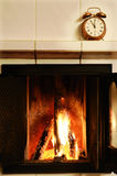 Fireplace and old-fashioned copper alarm clock on the mantelshe stock images