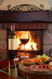Fireplace And Red Wine 2. Wine bottle and partially filled glass with assorted food on a wooden serving plate. Raging fire in fireplace in the background royalty free stock photos