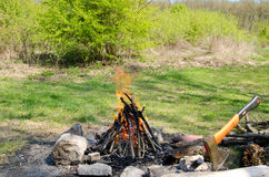 Fireplace of stone on green grass. For baking bacon and sausages Stock Image
