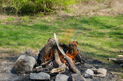 Fireplace of stone on green grass. For baking bacon and sausages Royalty Free Stock Photography