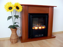 Fireplace and sunflowers. Three sunflowers in a wicker basket standing next to a modern fireplace Stock Image