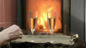 By the fireplace two glasses with champagne. Stand on a tray stock footage