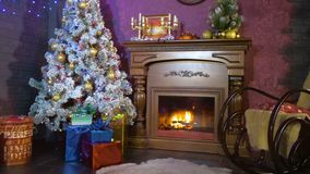 New year background. A warm fireplace with a view on a Christmas tree during new year night. stock video footage