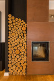 Fireplace and wood pieces. Cosy interior closeup with fireplace and wood storage space Royalty Free Stock Photography
